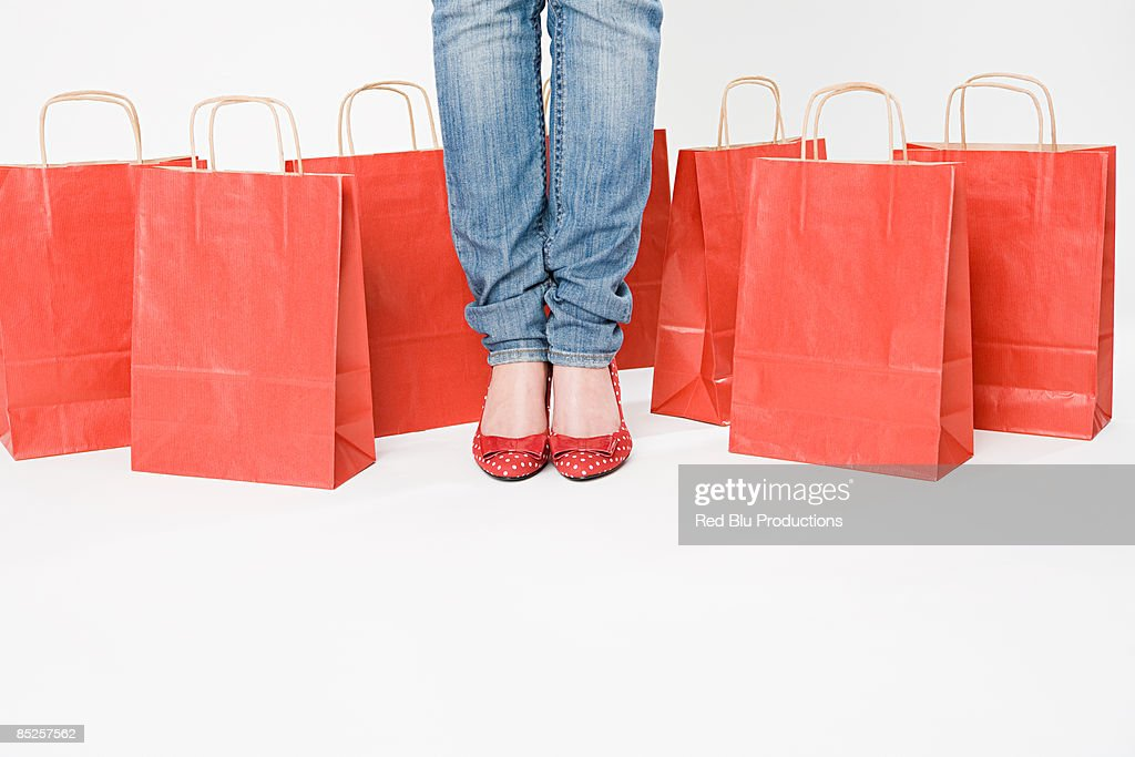 Woman standing with shopping bags : Stock Photo