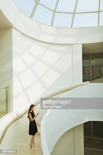 Woman standing with smart phone in building