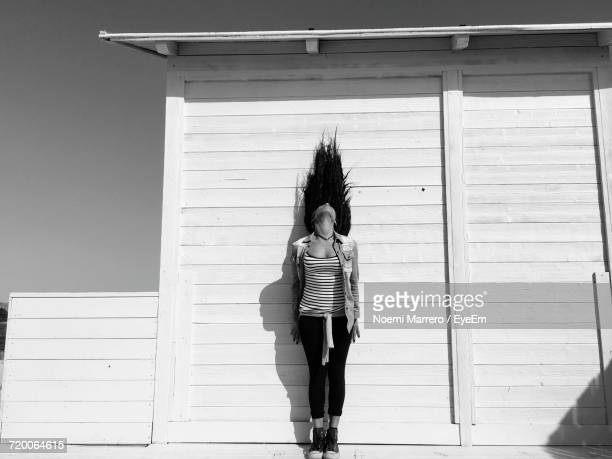 Woman Standing With Tousled Hair Against Cottage On Sunny Day