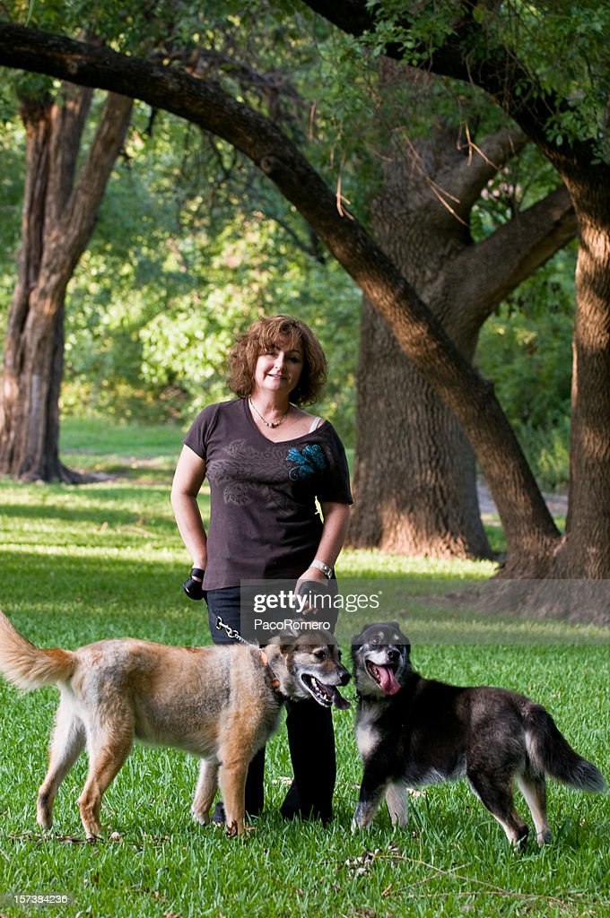 Woman standing with two dogs in park : Stock Photo