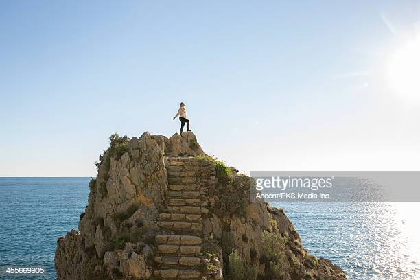 Woman stands alone on rocky summit above sea