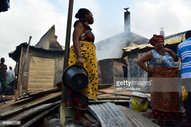 A woman stands amid debris in the market after a fire devastated the building during the night on September 18 2017 in Abobo neighborhood of Abidjan...