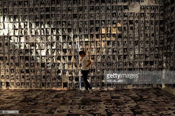 TOPSHOT A woman stands among photos taken of human rights victims during martial law displayed at an experimential museum inside a military camp in...