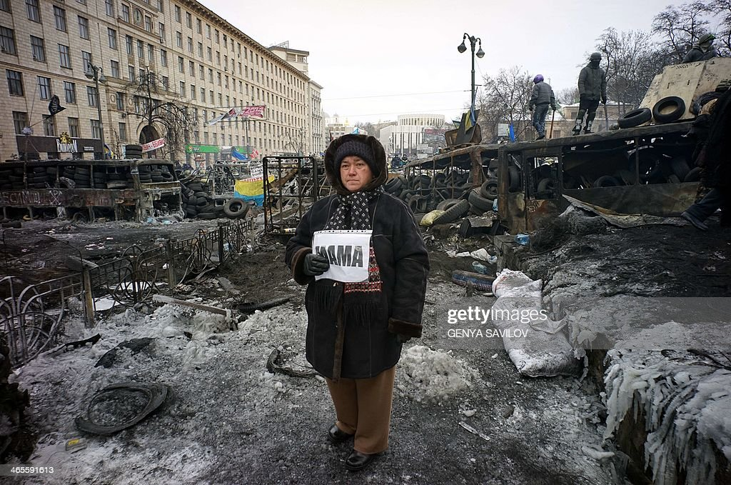 Woman stands among protesters barricades and riot police lines and holds the placards reading Mother, urging riot police troops stop fighting with protesters at the flashpoint Grushevsky Street in central Kiev on January 28, 2014. Ukraine lawmakers on Tuesday scrapped draconian anti-protest laws that have angered the opposition, in a move aimed at bringing a deadly two-month standoff to an end.