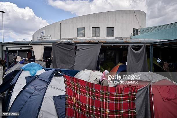 A woman stands among tents on May 18 2016 at the Piraeus port where some 1500 migrants and refugees live in a makeshift camps on passenger areas...