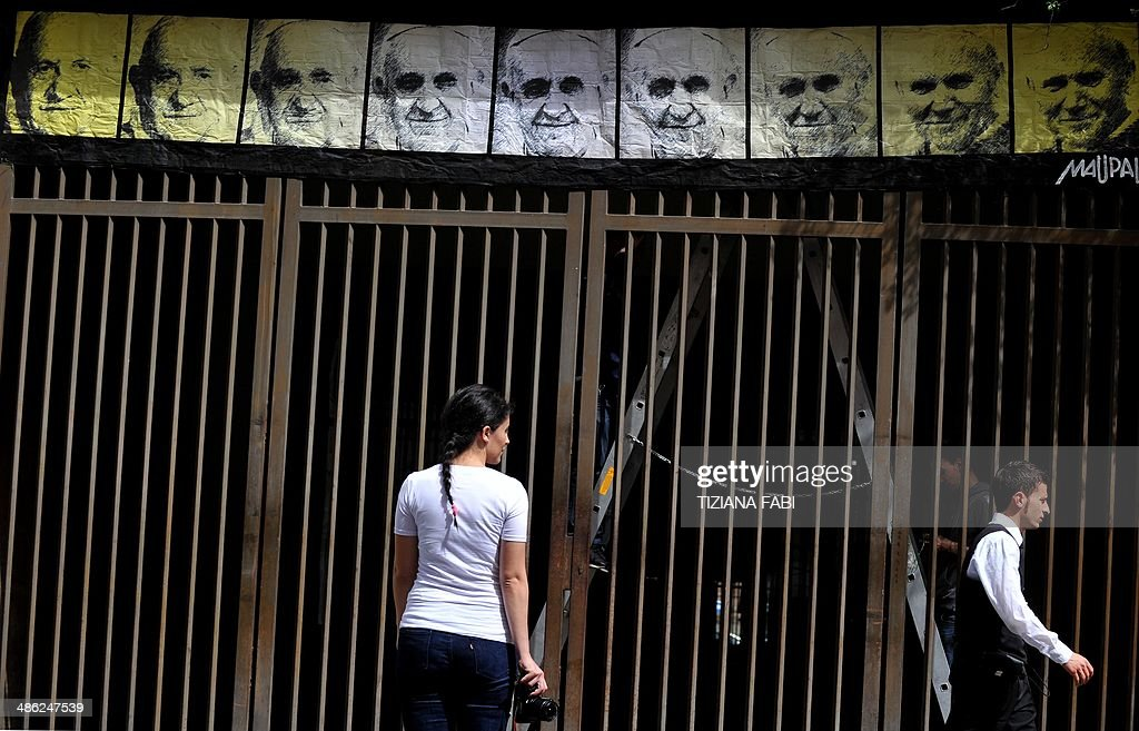 A woman stands as a man walks past a new work of an Italian street artist Maupal, a portrait of the three popes, Pope Francis (C) Pope John Paul II (R) and Pope John XXIII (L) on April 23, 2014 in Rome near the Vatican