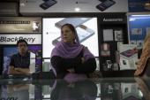 A woman stands as Apple Inc iPhone 5 and Blackberry Z10 advertisements are displayed in store in Connaught Place in New Delhi India on Saturday Feb...