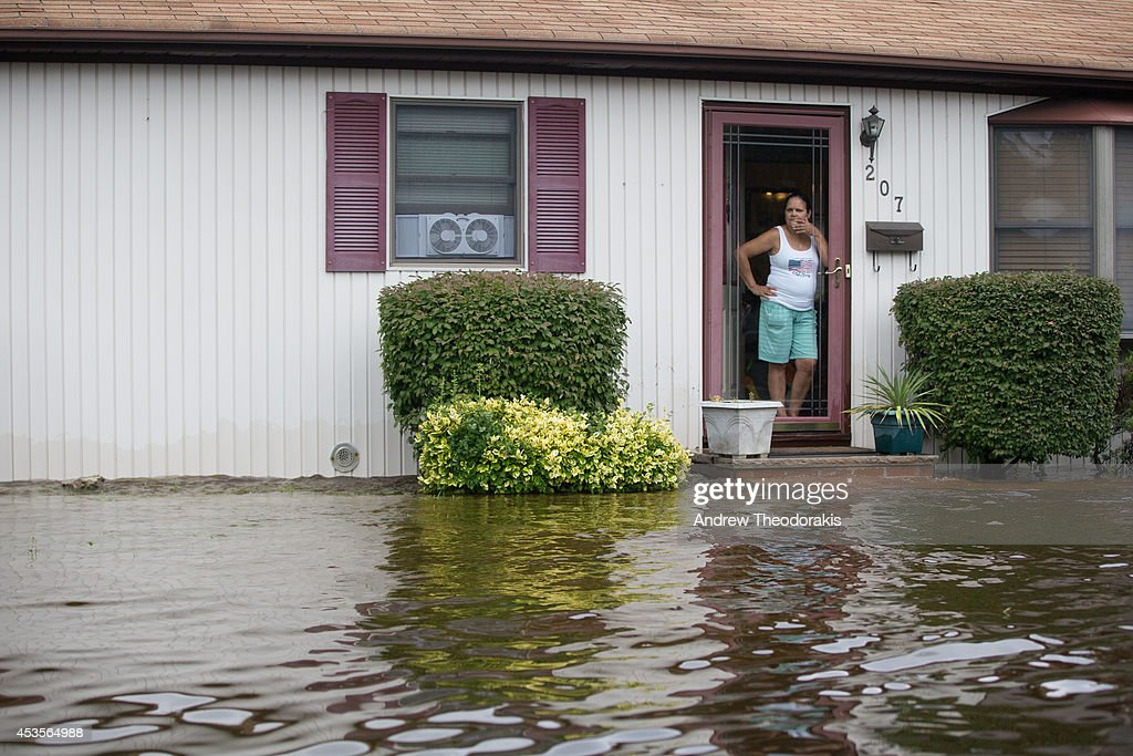 A woman stands at her doorway watching the water level rise on Moffit Blvd. following heavy rains and flash flooding August 13, 2014 in Islip, New York. The south shore of Long Island along with the tri-state region saw record setting rain that caused roads to flood entrapping some motorists.
