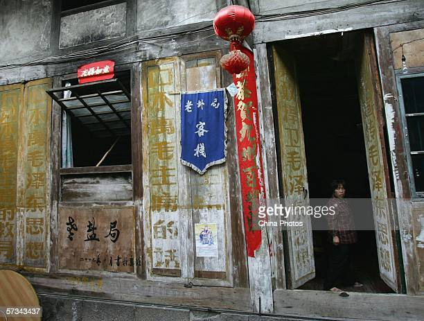 A woman stands at the door of an old house where slogans of the Cultural Revolution were painted on April 12 2006 in Gongtan Township of Youyang...