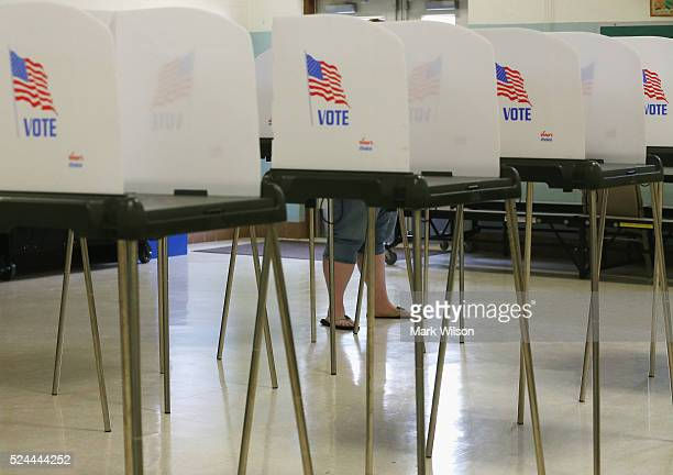 A woman stands at the voting booth at the White Marsh Elementary School polling station April 26 2016 in Mechanicsville Maryland Maryland is one of...