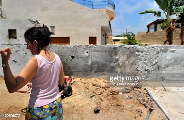 A woman stands at where his house used to stand after air strike by Hamas on July 21 2014 in Ashkelon Israel
