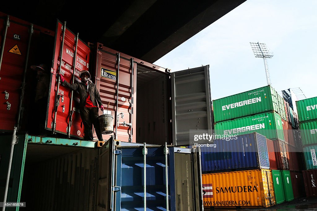 A woman stands atop an empty container at the Custom Global Service Co. container depot in Bangkok, Thailand, on Monday, Aug. 25, 2014. Thailand's trade figures are scheduled for release on Aug. 27. Photographer: Dario Pignatelli/Bloomberg via Getty Images