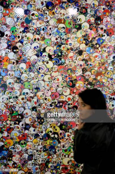 A woman stands before an art work of Haruki Murakami on June 12 2012 during the preview day of the Art 43 Basel fair and exhibition which will take...