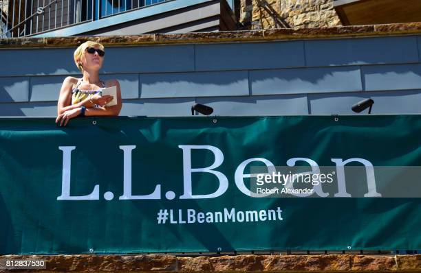 A woman stands behind a banner sign promoting the LL Bean clothing shop in Vail Colorado