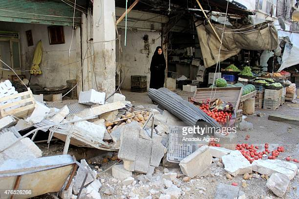 A woman stands behind the damaged counters at a local bazaar after a helicopter belonging to the Syrian Army bombed a residential areas in the...