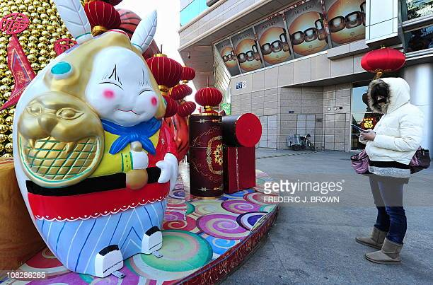 A woman stands beside a statue on January 18 2011 of Lord Rabbit known as Tuer Ye a traditional icon of the MidAutumn Festival but becoming ever...