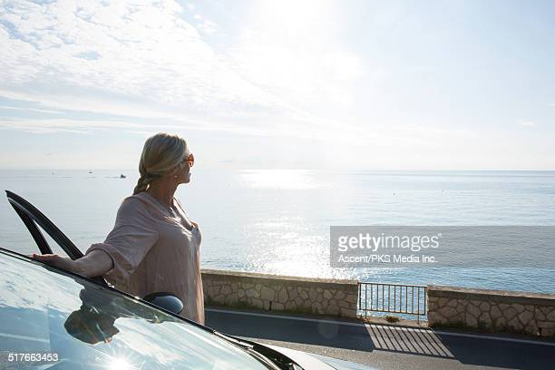 Woman stands beside car, looks out to sea