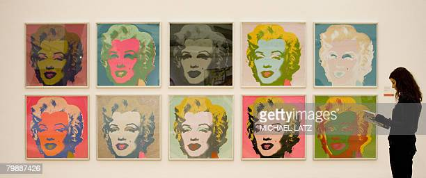 A woman stands beside the work 'Marilyn Monroe' by US artist Andy Warhol presented at the Staatsgalerie museum in Stuttgart southern Germany on...