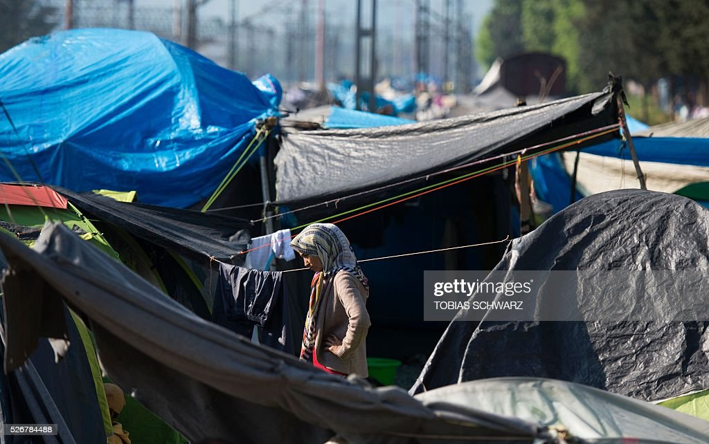 A woman stands between tents at a makeshift camp for migrants and refugees near the village of Idomeni not far from the Greek-Macedonian border on May 1, 2016. Some 54,000 people, many of them fleeing the war in Syria, have been stranded on Greek territory since the closure of the migrant route through the Balkans in February. / AFP / TOBIAS