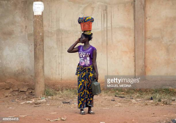 A woman stands by a road in the 'Combattant' district close to the airport in Bangui on December 25 2013 Heavy arms fire triggered panic on December...