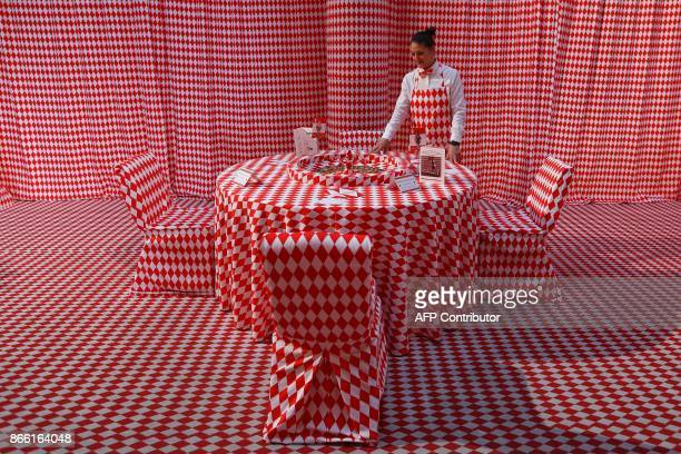A woman stands by a roulette's table decorated for the 'Let's fall in diamonds' exhibition by Belgian artist and designer Charles Kaisin at the...