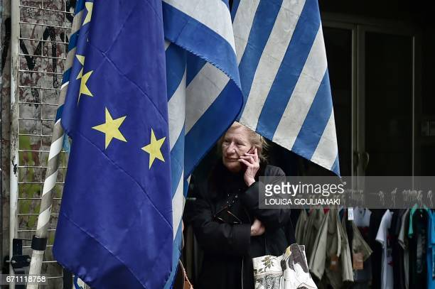 A woman stands by European Union and Greek flags in central Athens on April 21 2017 Greece in 2016 registered a primary surplus of 39 percent of...