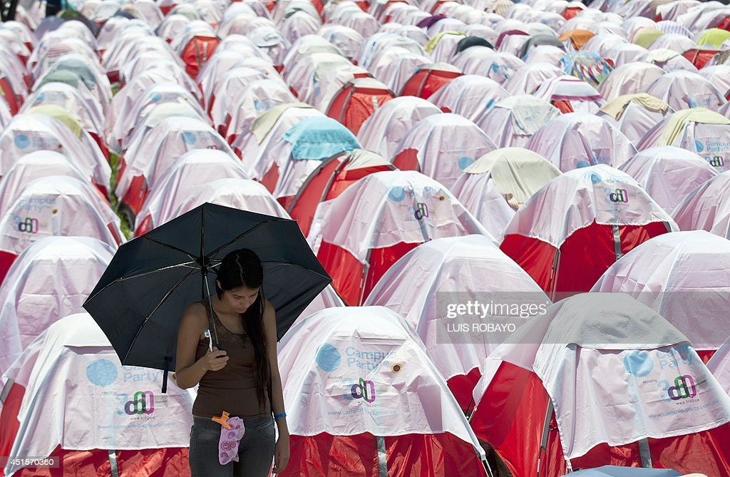 A woman stands by tents set up by the participants of the seventh edition of Colombia's Campus Party on July 1, 2014, in Cali, department of Valle del Cauca, Colombia. The Campus Party is considered the biggest event of technology, innovation, creativity, leisure and culture in the digital network world, and takes place for the first time in Cali, a city which is projected as one of the Smart Cities in Colombia and South America, given its initiatives in the area of technology, and sustainable development policy. AFP PHOTO / LUIS ROBAYO