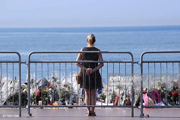 TOPSHOT A woman stands by the new makeshift memorial in tribute to the victims of the deadly Bastille Day attack at the Promenade des Anglais on July...