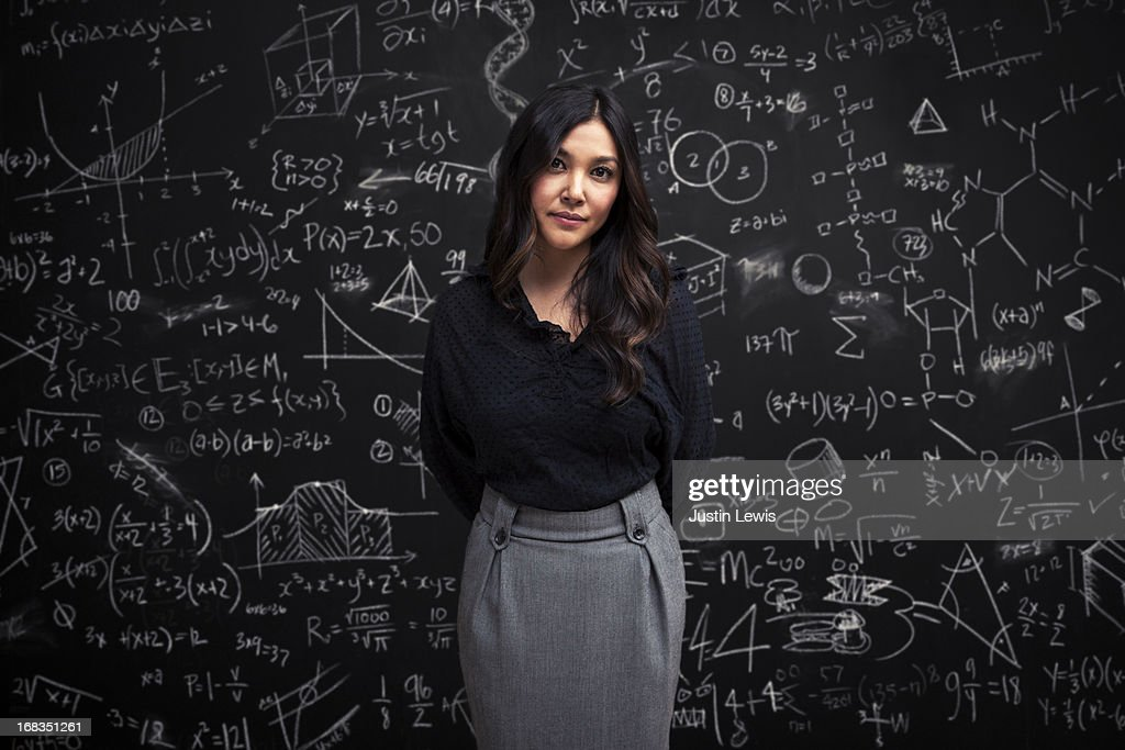Woman stands calm in front of math chalkboard