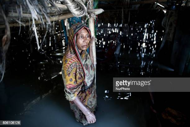 A woman stands highdeep in flood water inside her submarged house in Guthail Jamalpur Bangladesh on 19 August 2017