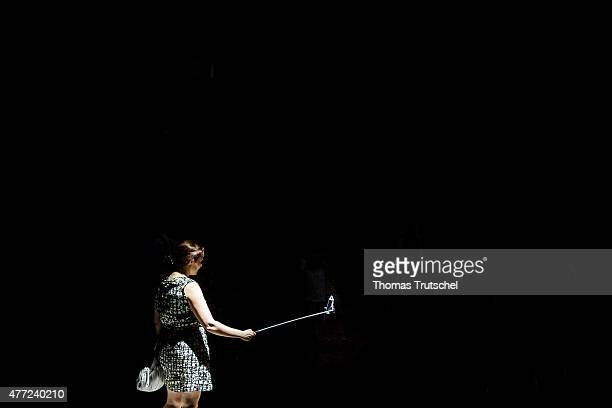 A woman stands in a beam of light and take a selfie using a selfie stick on June 11 in Rome Italy