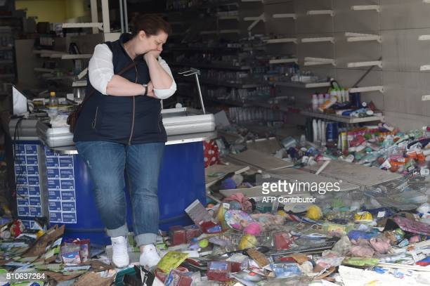 A woman stands in a looted Budnikowsky drugstore after riots in Hamburg's Schanzenviertel district on July 8 2017 in Hamburg northern Germany where...