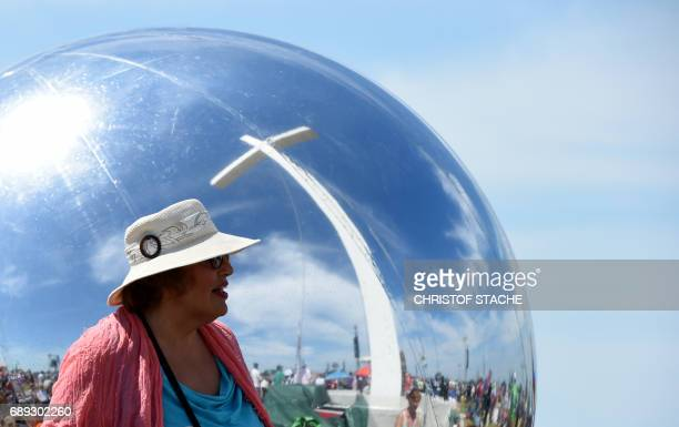A woman stands in front of a ball with a reflecting surface during the final mass of the Kirchentag festival celebrating the 500th anniversary of the...