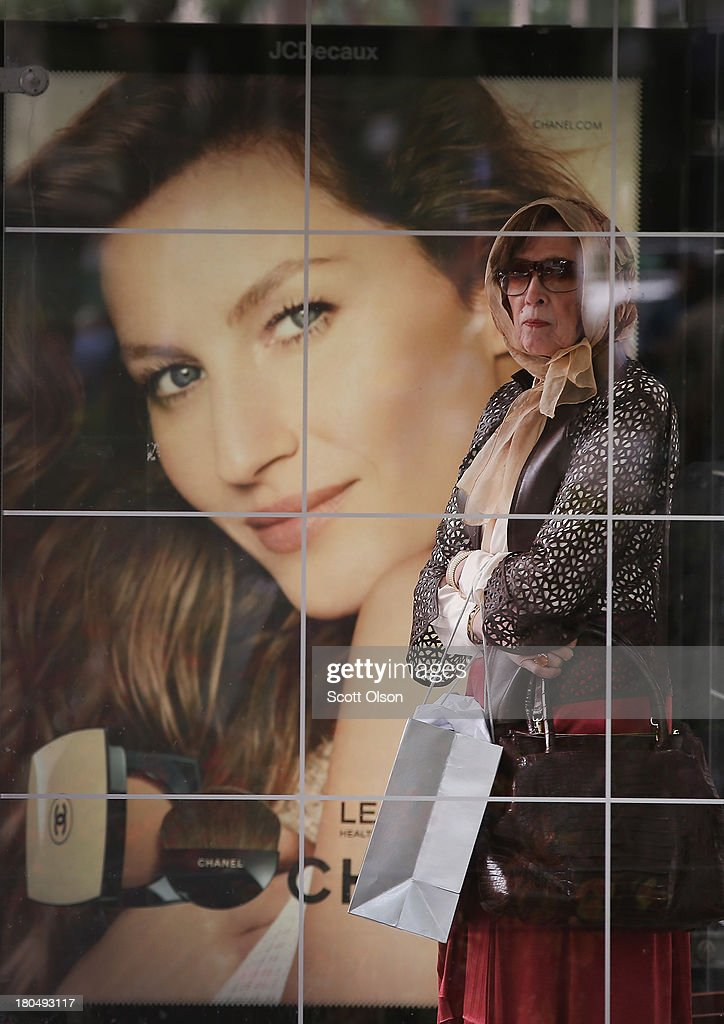 A woman stands in front of a Chanel ad on a bus stop along the Magnificent Mile shopping district on September 13, 2013 in Chicago, Illinois. According to the Commerce Department retail sales rose a seasonally adjusted 0.2 percent in August from the previous month, short of the 0.5 percent anticipated by economists.