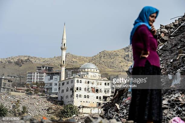 TOPSHOT A woman stands in front of a damaged mosque as she arrives in Sirnak city on November 14 2016 after a 246day curfew was partially lifted The...