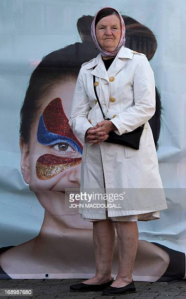 A woman stands in front of a Eurovision logo at a Eurovision public viewing area in downtown Malmo ahead of the finals of the 2013 Eurovision Song...