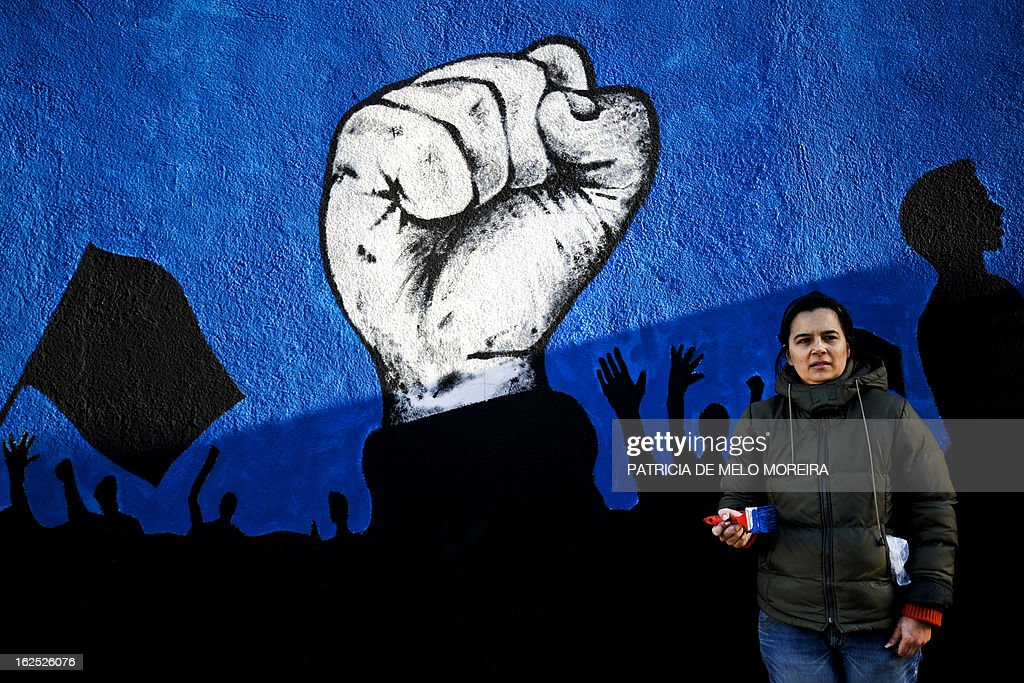 A woman stands in front of a mural calling for participation in an anti-government demonstration, in Lisbon on February 24, 2013. The mural by the 'Damn the Troika' movement calls for participation in a protest against the Portuguese government austerity measures in Lisbon on March 2. AFP PHOTO / PATRICIA DE MELO MOREIRA