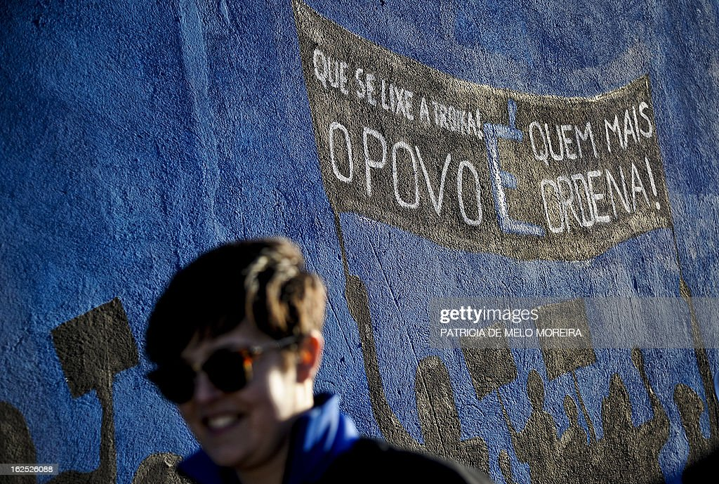 A woman stands in front of a mural reading 'Damn theTroika! The power lies in the People' in Lisbon on February 24, 2013. The mural by the 'Damn the Troika' movement calls for participation in a protest against government's austerity measures in Lisbon on March 2. AFP PHOTO / PATRICIA DE MELO MOREIRA