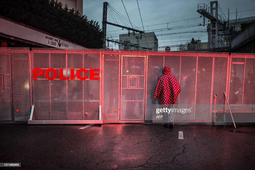 A woman stands in front of a police barricade during a demonstration against the new LGV Lyon-Turin project, on December 3, 2012 in Lyon, on the sideline of the 30th France-Italy annual summit.