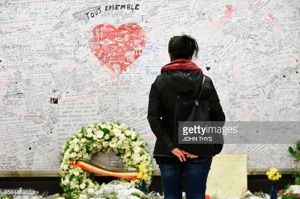 TOPSHOT A woman stands in front of a remembrance wall on March 22 2017 at the Maelbeek Maalbeek subway station in Brussels during the commemorations...