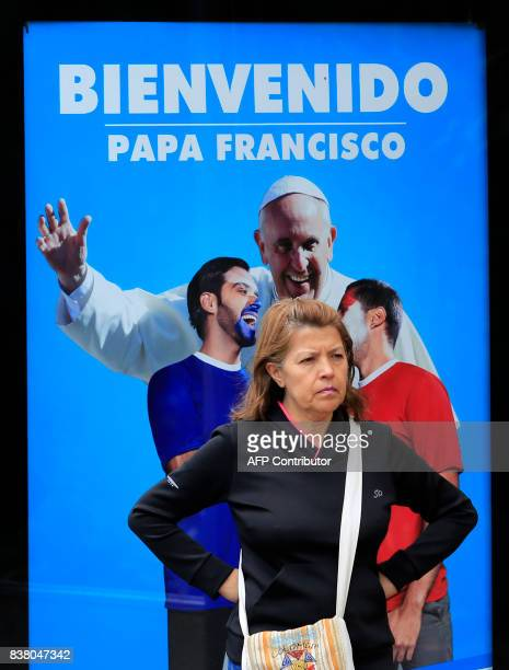 A woman stands in front of a sign welcoming Pope Francis ahead of his upcoming visit in Bogota on August 23 2017 Pope Francis will make a special...