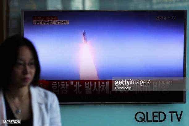 A woman stands in front of a television screen showing a news broadcast on North Korea's ballistic missile launch at Seoul Station in Seoul South...