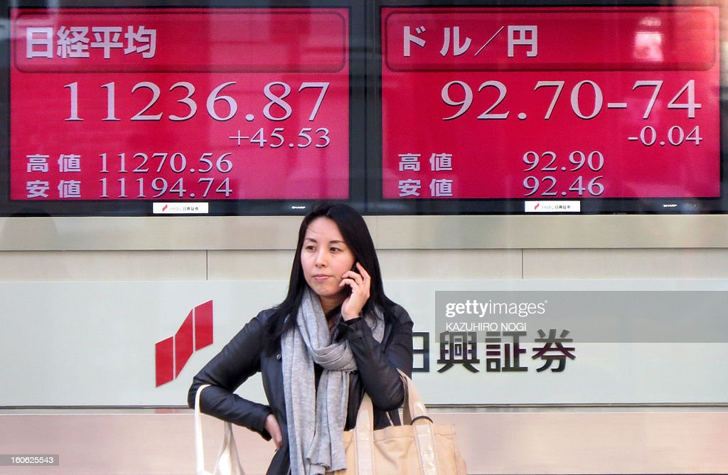 A woman stands in front of an electronic board flashing the numbers of the Tokyo Stock Exchange (L) and the foreign exchange rate of the yen against one US dollar (R) in Tokyo on February 4, 2013. Tokyo stocks were 0.48 percent higher on February 4 morning, on the back of lingering optimism over a sharp rally on Wall Street which pushed close to new records.
