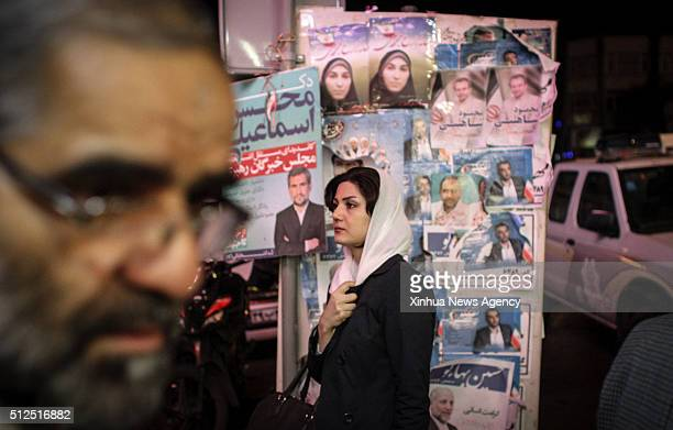 A woman stands in front of electoral posters a day before election in downtown Tehran Iran on February 25 2016 Two major political factions will...