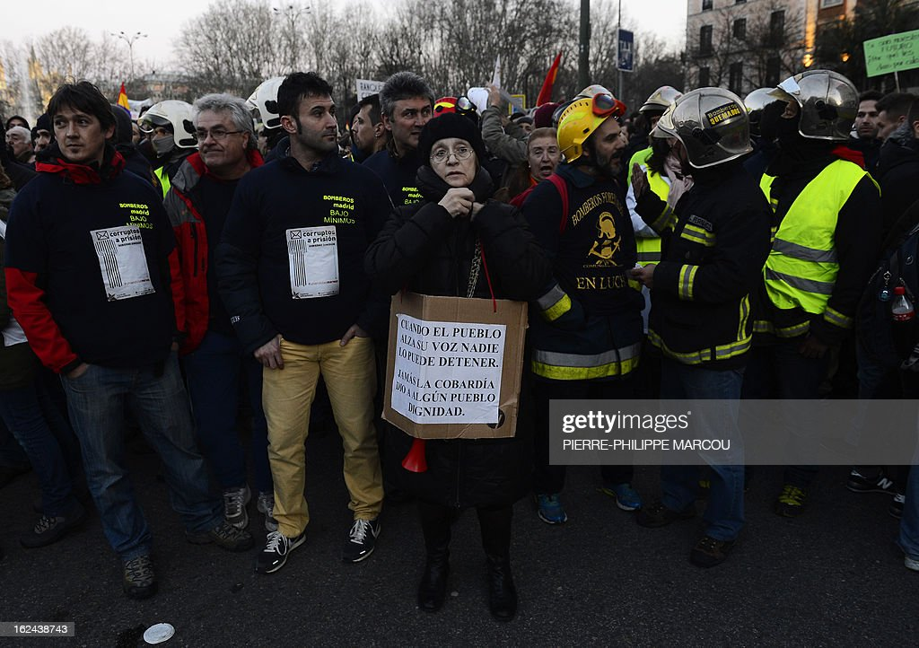 A woman stands in front of firefighters as they take part in a protest against government austerity measures on February 23, 2013 in Madrid. Nurses, doctors, students, miners and members of Spain's 'indignant' movement against economic inequality join in the so-called 'citizens' tide' against the steep spending cuts and tax hikes imposed by Prime Minister Mariano Rajoy's conservative government to slash the public deficit. The day of protest coincides with the 31st anniversary of the failure of right-wing military coup that sought to crush Spain's young democracy and restore military rule. The placard reads: 'When the People raises his voice no one can stop it. Cowardice never gave any People dignity.'