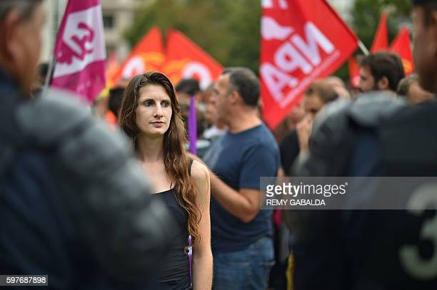 A woman stands in front of French Policemen during a protest against the Labour law reform organised by French trade unions and youth associations in...