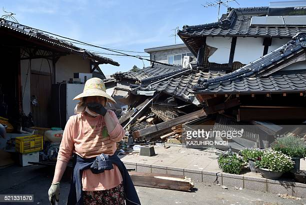 TOPSHOT A woman stands in front of her damaged house in Mashiki Kumamoto prefecture on April 15 after a 65magnitude quake struck the southwestern...