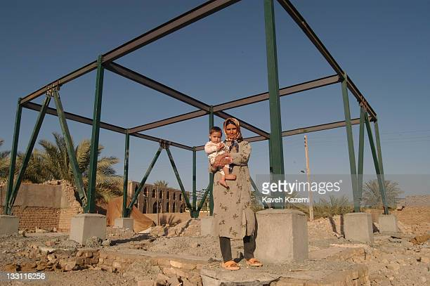 A woman stands in front of her new home structure after a major earthquake Bam Iran 7th November 2004 Her son Ali was born the moment the quake...