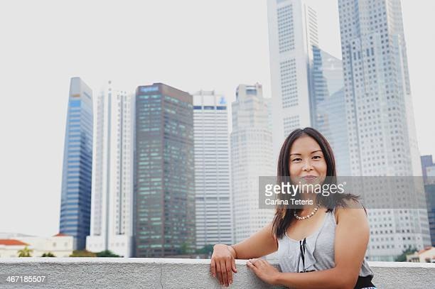 Woman stands in front of Singapore skyline