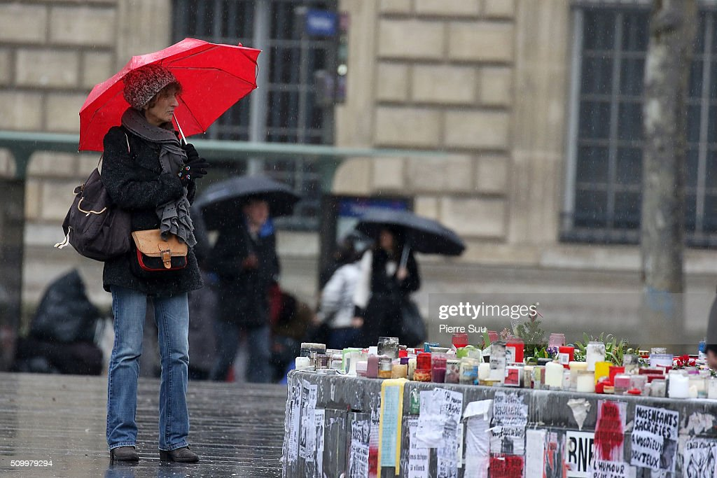 A woman stands in front of the monument at the Republique square on February 13, 2016 in Paris, France. People continue to leave tributes to victims three months after the Paris terrorist attacks.